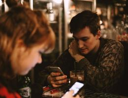 millennial man & woman with phones