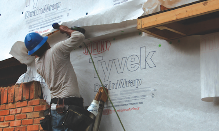 Construction worker installing housewrap on a house