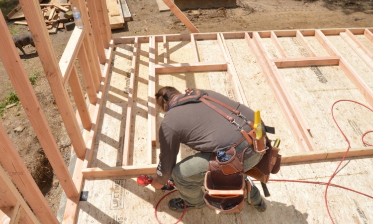 Carpenter Ben Bogie framing the walls of the model remodel project