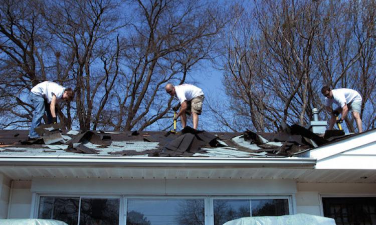 Men on residential roof remove asphalt shingles.