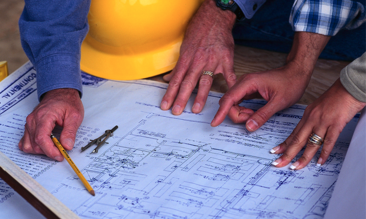 Production manager reviewing plans with client