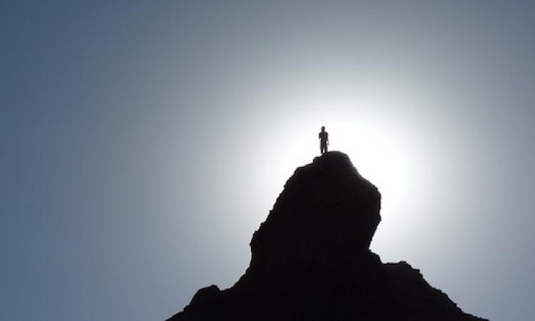 Photo of man atop mountain, without peer, all alone.