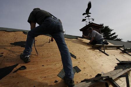 Men installing asphalt shingles